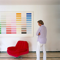 Portrait of artist and designer Nicholas Alvis Vega standing in front of one of his colour-field paintings