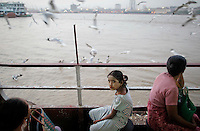 People travel on a ferry across the river in Yangon March 29, 2012.  REUTERS/Damir Sagolj (MYANMAR)