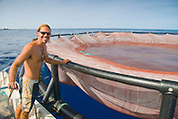 Kona Blue Water Farms worker and one of the floating open ocean fish pens which is used to raise juvenile Kona Kampachi, Hawaiian yellowtail, aka almaco jack or kahala, Seriola rivoliana, off Kona Coast, Big Island, Hawaii, Pacific Ocean