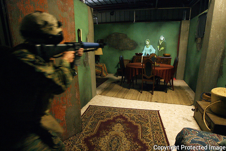 A Marine bursts into a room of a simulated Iraqi house and quickly makes a determination if the images of house residents projected on the wall are a threat during training exercises at Camp Pendleton, California in January of 2008.  photo for North County Times