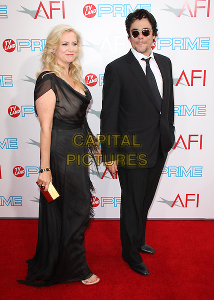 LAURA BICKFORD & BENICIO DEL TORO.37th Annual AFI Lifetime Achievement Awards held at Sony Pictures Studios, Culver City, California, USA..June 11th, 2009.full length black sheer dress suit sunglasses shades hand in pocket gold clutch bag .CAP/ADM/KB.©Kevan Brooks/AdMedia/Capital Pictures.