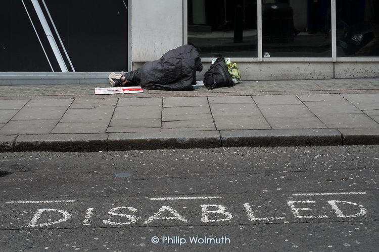 Rough sleeper sleeping on the pavement in a street close to Oxford Street, central London.