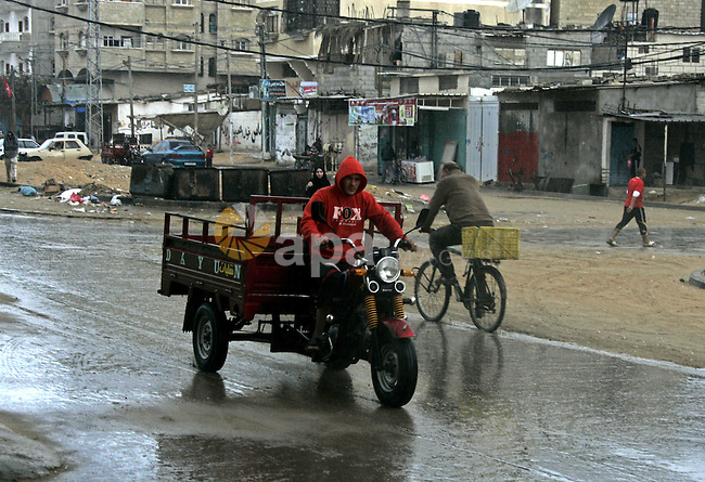 A Palestinian man rides a Tuk-Tuk, a three-wheel vehicle, in a street during the fall of rains in the Rafah refugee camp in the southern Gaza Strip on December 6, 2010. Rain delayed on the Middle East region for the usual season. Photo by Abed Rahim Khatib