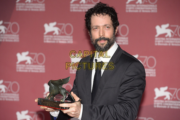 Noaz Deshe<br /> at the Award Winners Photocall during the 70th Venice International Film Festival, Palazzo del Casino in Venice, Italy, September 7th 2013.<br /> half length black suit beard facial hair tie trophy award winner trophy<br /> CAP/ZZG<br /> &copy;ZZG/Capital Pictures
