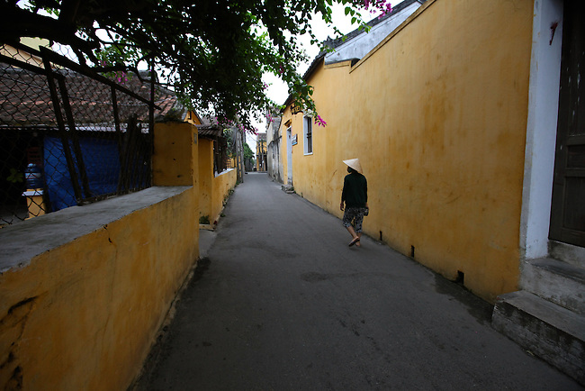 A woman walks down an empty alley early one morning in Hoi An, Vietnam. The city was an important colonial trading port from the 15th to the 19th centuries, and the architecture of Hoi An Ancient Town is the most well-preserved in Vietnam. April 22, 2012.
