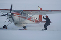 Eagle Island lead checker Jim Gallea helps pilot Bruce Moroney turn his plane by holding the strut rope at the Eagle Island checkpoint on Saturday afternoon.   Iditarod 2009