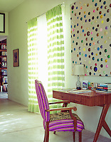 A large abstract painting with a compostion of coloured dots is displayed above a writing desk with a chair covered in vibrant pink stripes