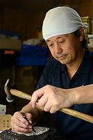 "Tatsushi Yamagawa working on an art piece that will feature a ""wood grain"" effect created in metal. Gyokusendo, Tsubame, Niigata Pref, Japan, August 24, 2017. Traditional copper metalworking company Gyokusendo was founded in 1816 and is a registered as a traditional craft of Japan. At Gyokusendo, in a highly-skilled craft process, complex items such as teapots are beaten from a single sheet of copper using hammers and hundreds of other specialist tools."
