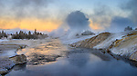 Yellowstone National Park, Wyoming: Pre-dawn light on steaming geysers and reflections along the Firehole River in the Upper Geyser Basin