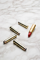 Bullets and lipstick laying on a marble surface