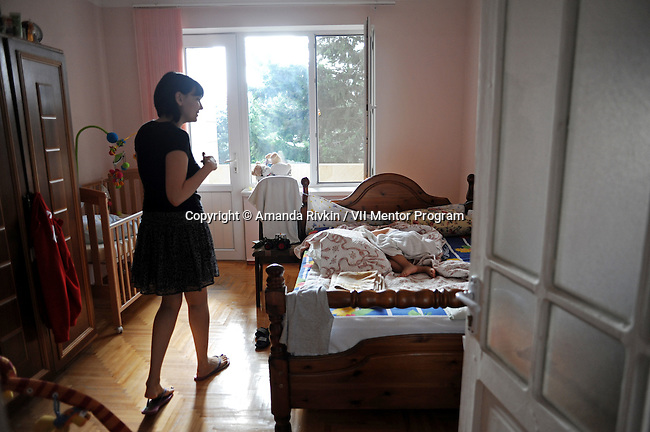 Nika Azimova, the wife of the deputy foreign minister, goes to kiss her son as he naps in her dacha at Government Resort Number Two in Zagulba, Azerbaijan on September 25, 2011.
