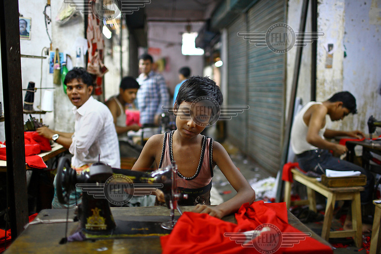 Ten-year-old Johirul sews t-shirts in a Dhaka factory. He works a 12 hour day and is paid less than GBP 9 per month.