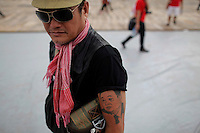 A man sports a tattoo of ousted premier Thaksin Shinawatra as his and supporters of his sister Yingluck gathe for the last big pre-election rally for their Puea Thai (For Thais) party at a stadium in Bangkok July 1, 2011. Thailand holds a general election on July 3 that might  be a step on the road to stability after five years of political turbulence. But it could just as easily prolong the rcrisis, especially if there is no clear-cut winner.  REUTERS/Damir Sagolj (THAILAND)