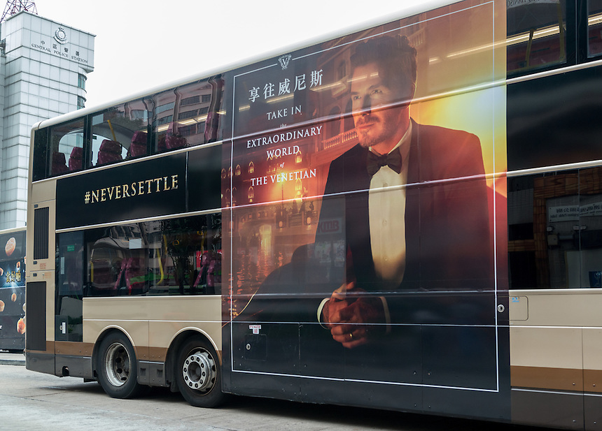 David Beckham's ad campaign for the Sands Group casino- The Venetian Hotel Macau. The #Neversettle campaign could be seen to promote gambling so the ad is careful to not to mention &quot;casino&quot; only &quot;hotel&quot;. Never settle has been seen as an irresponsible attitude to gambling as in &quot;Never settle up&quot; The ad is on the side of several Kowloon Motor Bus co. (KMB) buses terminating at the Macau Ferry Terminal Sheung Wan Hong Kong. <br /> 11.03.15. 11th March 2015.