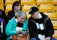 Swansea City fans check the score the early kick-off during the Barclays Premier League match between Norwich City and Swansea City played at Carrow Road, Norwich on November 6th 2015