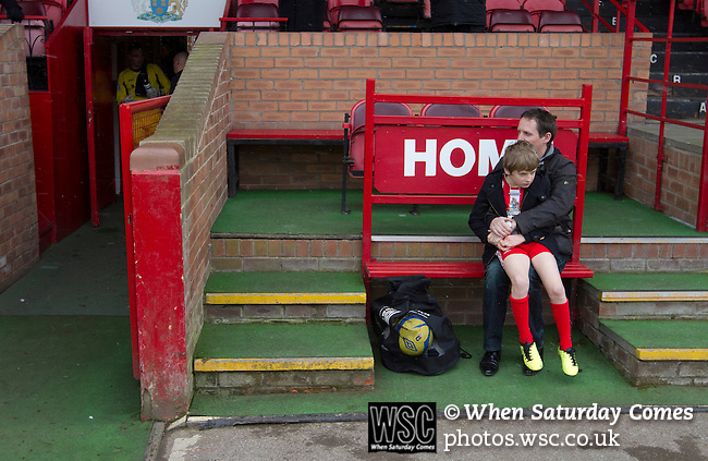 Altrincham 2 Worcester City 0, 23/03/2013. Moss Lane, Blue Square Bet North. The home team's mascot and his father struggle to keep warm before the Blue Square Bet North fixture between Altrincham and Worcester City at Moss Lane, Altrincham. The home team won the match 2-0 watched by 777 spectators on a day when most non-League football in England was cancelled due to adverse weather. Altrincham were historically one of the major English non-League teams but have never been promoted to the Football League. Photo by Colin McPherson.