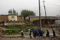 Girls run for shelter after a sudden rainstorm rolls onto the city of Faizabad.