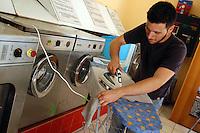 Giovani studenti e neolaureati lavorano in una lavanderia a gettoni..Young students and graduates working in a laundromat..