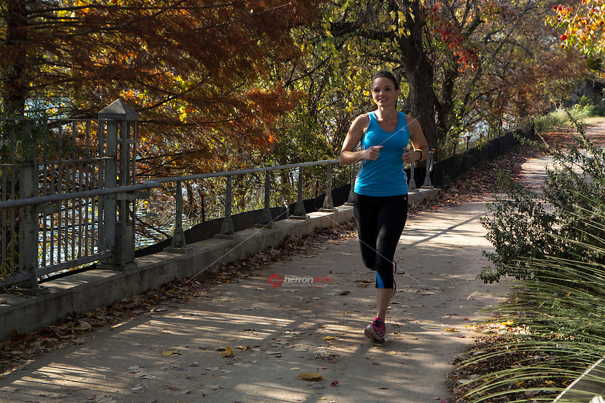 Fitness Female Runner running on trail thru The Lady Bird Lake Hike and Bike Trail in fall in downtown Austin, Texas