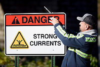 NWA Democrat-Gazette/DAVID GOTTSCHALK Bob Dow, road assessment specialist with the Benton County Road Department, places one of six strong currents warning signs Friday, November 1, 2019, on the bank of the War Eagle creek at the War Eagle Mill. The signs, were placed by Benton County and Bob Tharp, the mayor of Decatur, in a collaborated project to bring awareness of the dangerous currents on the creek. Bob Tharp and his wife Joy's Ross died in a floating accident at the dam on the river in June of this year.