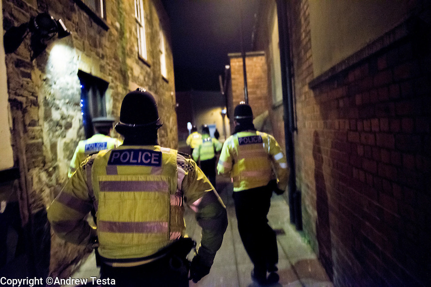 UK. Northampton. 7th December 2013<br /> Police run down an alley in downtown Northampton after a fight is reported.<br /> &copy;Andrew Testa for the New York Times