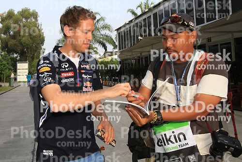 KUALA LUMPUR, MALAYSIA - MARCH 28: Redbull driver Sebastian Vettel of Germany sign autograph for a fan ahead of the first practice session during the Malaysia Formula One Grand Prix at the Sepang Circuit on March 28, 2014 in Kuala Lumpur, Malaysia. (Photo by PETER LIM/PhotoDesk.com.my)