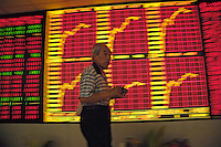 A Chinese investor walks past stock index in a stock exchange of Beijing. China's bullish stock market shrugged off the central bank's most aggressive monetary tightening this year, hitting a fresh all-time high as individual investors poured money into shares..21 May 2007