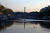 A view of the port de l'Arsenal in Paris (it links the Canal de Saint Martin to place de la Bastille), with its boats, its typical bridge, and the column of July which reflects itself onto the basin water on the background, in the sunrise light. The water surface is slightly rippled by some ducks, the profile of one of which stands out. Digitally Improved Photo.