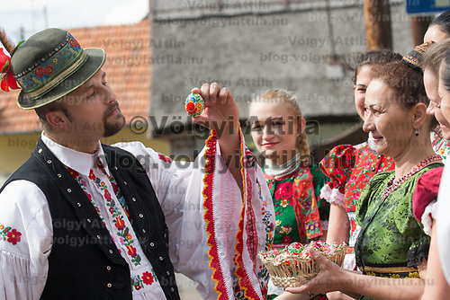 Man looks at a painted egg received from women after watering them as part of the Easter fertility traditions wearing traditional dresses of the Matyo people during the celebration in Mezokovesd (about 130 km East of capital city Budapest), Hungary on April 13, 2017. ATTILA VOLGYI