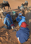 Camel trekking through the sand dunes of Merzouga, Morocco. Taureg guides trying to sell souvenir items.