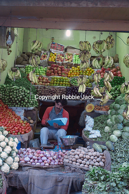 A shop keeper selling fruit and vegatables in Manali.in the Kullu Valley, Himachal Pradesh, India.