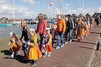 Koningsdag in Marken. Tijdens Koningsdag dragen veel inwoners van Marken klederdracht met oranje accenten. Optocht in klederdracht door het dorp