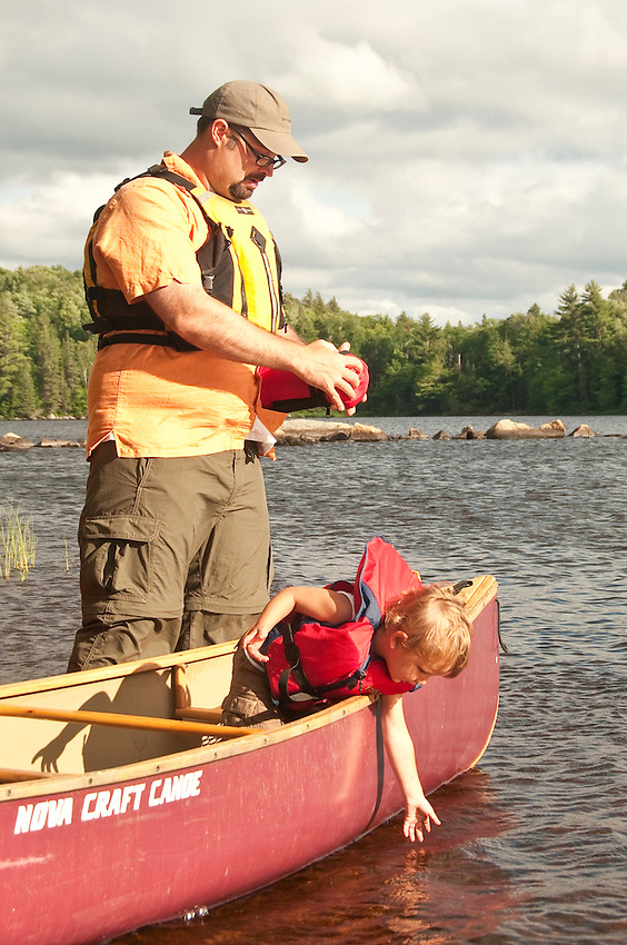 A young family goes canoeing while camping at Craig Lake State Park near Michigamme Michigan.