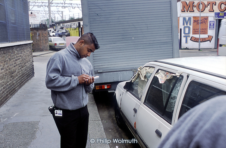 Neighbourhood Warden employed by Tower Hamlets Council inspects a dumped car in Bethnal Green.