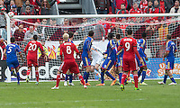 Toronto, Ontario - April 12, 2014: Toronto FC midfielder Kyle Bekker #8 takes a free kick which just hits the bar of the net during the 2nd half in a game between the Colorado Rapids and Toronto FC at BMO Field in Toronto.<br />
