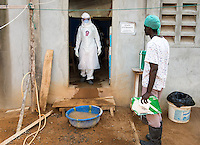 "Health care workers prepare to enter the ""red zone"" to care for patients at the ELWA II Ebola Treatment Unit (ETU) in Monrovia, Liberia on Sunday, March 1, 2015. Occidental College professor Mary Beth Heffernan's PPE Portrait Project involves photographing health care workers and making disposable, adhesive prints of their images, which are then placed on the worker's PPE.<br /> ELWA II has one of the largest numbers of Ebola patients in Liberia at the moment and was the first ETU to open in Monrovia, Liberia's capital city.<br /> (Photo by Marc Campos, Occidental College Photographer) Mary Beth Heffernan, professor of art and art history at Occidental College, works in Monrovia the capital of Liberia, Africa in 2015. Professor Heffernan was there to work on her PPE (personal protective equipment) Portrait Project, which helps health care workers and patients fighting the Ebola virus disease in West Africa.<br />
