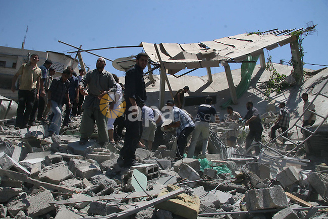 Palestinian police and civilian defense members inspect the rubble of a building after an explosion in Beit Lahia, the northern Gaza Strip. At least four have been reportedly killed and 40 wounded after a blast that leveled a house in northern Gaza. According to reports witnesses said the explosion was the result of a air strike, although Israel is denying any military strikes.