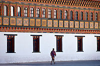 A man walking next to the Tashichho Dzong, home of the Government, Royal Palace and Religious Centre, in Thimpu, Bhutan