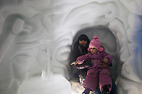 Moscow, Russia, 14/01/2012..A woman and child inside tunnels in Moroz City, or Frost City, an ice town constructed in Moscow's Sokolniki Park by a team of architects and ice sculptors. As well as ice sculptures the temporary town features a disco, hotel, fitness centre, post office and prison.