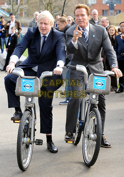 BORIS JOHNSON & ARNOLD SCHWARZENEGGER.Mayor of London; Governor of California.meet to try Barclay's Cycle Hire Scheme and to discuss how to drive markets forward for low and zero emission technologies..Tower Bridge, London, England,.March 31st 2011..Arnie full length black grey gray suit tie navy riding bike bicycle hand pointing .CAP/WIZ.© Wizard/Capital Pictures.