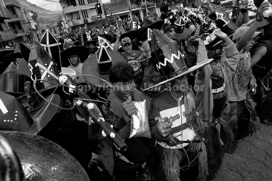 Indians, wearing black cardboard hats, dance and shout furiously during the Inti Raymi (San Juan) festivities in Cotacachi, Ecuador, 24 June 2010. 'La toma de la Plaza' (Taking of the square) is an ancient ritual kept by Andean indigenous communities. From the early morning of the feast day, various groups of San Juan dancers from remote mountain villages dance in a slow trot towards the main square of Cotacachi. Reaching the plaza, Indians start to dance around. They pound in synchronized dance rhythm, shout loudly, whistle and wave whips, showing the strength and aggression. Dancers from either the upper communities (El Topo) or the lower communities (La Calera), joined in respective coalitions, seek to conquer and dominate the square and do not let their rivals enter. If not moderated by the police in time, the high tension between groups always ends up in violent clashes.