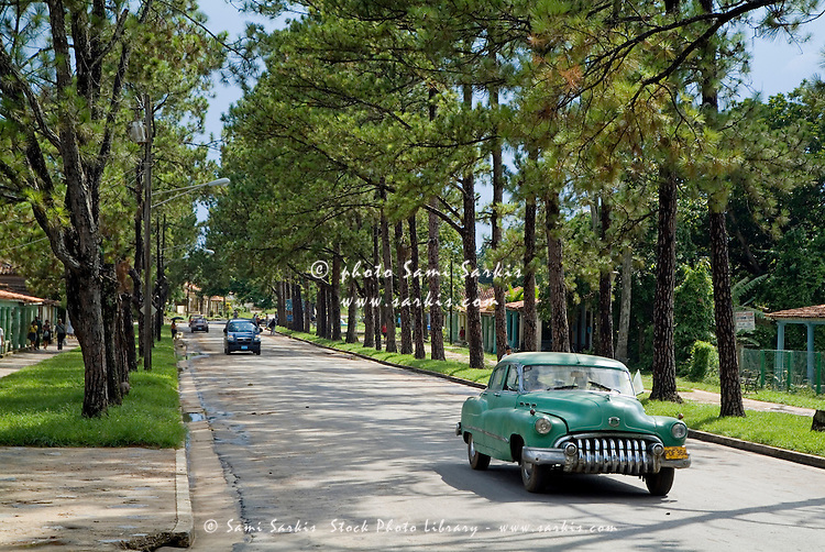 Classic American car driving along a treelined street in Vinales, Pinar del Rio Province, Cuba.