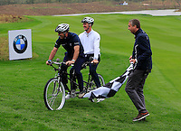 Paul McGinley (IRL) and Justin Rose (ENG) take to the tandem bike against Ian Poulter (ENG) and Wu Ashun (CHN) in the BMW i8 for a challenge during Wednesday's Pro-Am Day of the 2014 BMW Masters held at Lake Malaren, Shanghai, China 29th October 2014.<br /> Picture: Eoin Clarke www.golffile.ie