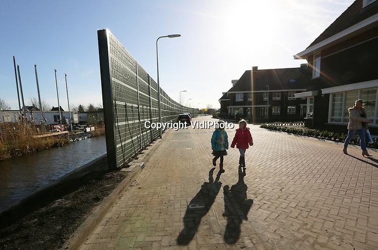 Foto: VidiPhoto<br /> <br /> REEUWIJK - Een zogenoemd noice-stop-geluidsscherm aan de Edisonstraat in Reeuwijk. De innovatieve geluidswal van Mobilane uit Leersum voorkomt in de nieuwbouwwijk niet alleen de herrie van de aannemer aan de overkant van het water, maar ontneemt ook het zicht op de rommel op het terrein.