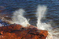 Waves of the Northumberland Strait crashing on red rocks