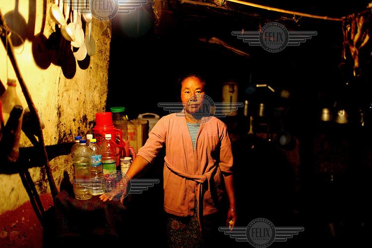 A woman stands inside her shack in the kala bazaar slum.