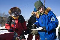 4-time Iditarod Champion Susan Butcher checks in Doug Swingley @ Ruby Chkpt 2006 Iditarod Alaska Winter