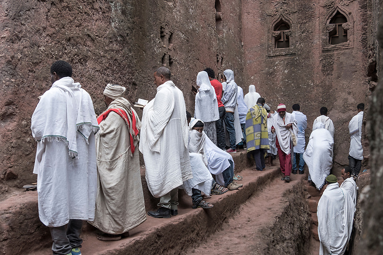 Worshipers offer morning prayer at the wall of one of Lalibela's rock-hewn churches.