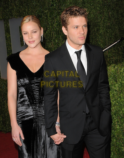 ABBIE CORNISH & RYAN PHILLIPPE.The 2009 Vanity Fair Oscar Party held at The Sunset Tower Hotel in West Hollywood, California, USA..February 22nd, 2009.oscars half length black dress silk satin suit holding hands hand in pocket couple .CAP/DVS.©Debbie VanStory/Capital Pictures.