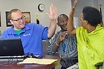 Tom Melissen (left), a senior account manager with Staff Management/SMX, gives a high five to Felecite Mukagatana after the woman was offered employment in the Mars factory in Elizabethtown, Pennsylvania. Joseph Shilalo, an employment specialist for Church World Service, looks on. Mukagatana is a refugee from the Democratic Republic of the Congo, and was resettled in Lancaster, Pennsylvania, by Church World Service, an agency that resettles refugees in Pennsylvania and other locations in the United States. <br /> <br /> Photo by Paul Jeffrey for Church World Service.
